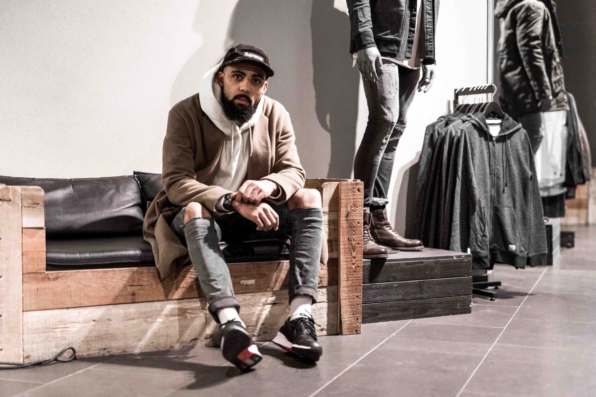 Jean-Claude Mpassy sitting inside the JAck & Jones Store in Vienna